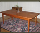 Our Cherry Dining Table has classic lines and a small drawer